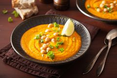 Creamy carrot chickpea soup on dark rustic background stock photos