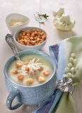 Creamy cauliflower soup in a blue cup with croutons and parmesan Stock Photos