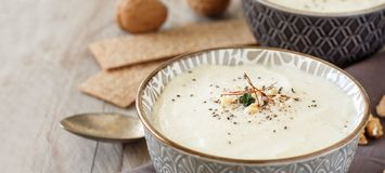 Creamy cauliflower soup. In a bowl on a wooden background Stock Photo