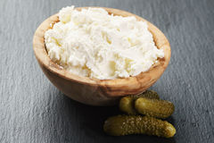 Creamy cheese in wooden bowl with small cucumbers Royalty Free Stock Image