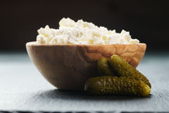 Creamy cheese in wooden bowl with small cucumbers Stock Photo