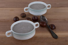 Creamy chestnut soup on wooden background Stock Images