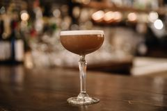 A creamy coffee cocktail with a bar in the background royalty free stock photo