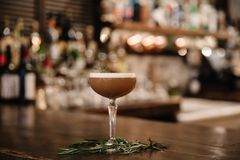A creamy coffee cocktail with a bar in the background stock photography