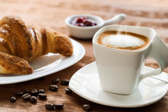 Creamy cup of coffee with croissant in background. Stock Photos