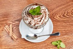 Creamy dessert with chocolate chips, decorated with a sprig of mint, standing on a saucer with a napkin and a spoon. Next to cinnamon and mint, close up, top stock photography