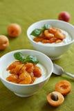 Creamy dessert with stewed apricot halves. Yoghurt with stewed apricot halves in white bowls royalty free stock photos