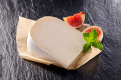 Creamy full milk white goat cheese. Served in a wedge with sliced ripe sweet figs on a dark textured slate counter top royalty free stock photo