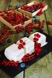 Ice cream with red currant berries. Creamy ice cream and boxes with red currants on an old wooden table Royalty Free Stock Photos