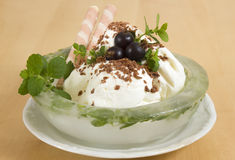 Creamy ice cream. Milk dessert in an ice plate with a melissa Stock Photos