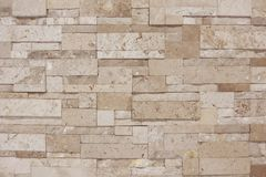 Creamy light brown textured tile wall with lighting from top. Background Stock Photography