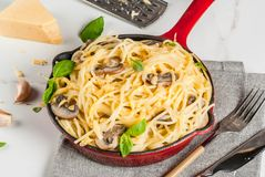 Creamy mushroom pasta. With cheese and basil, in portioned frying pan, on white marble table, copy space Stock Image