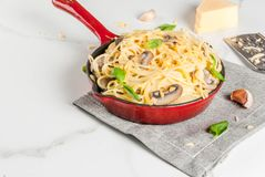 Creamy mushroom pasta. With cheese and basil, in portioned frying pan, on white marble table, copy space Stock Photo