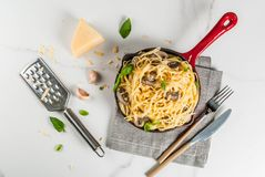 Creamy mushroom pasta. With cheese and basil, in portioned frying pan, on white marble table, copy space top view Royalty Free Stock Images