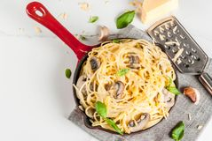 Creamy mushroom pasta. With cheese and basil, in portioned frying pan, on white marble table, copy space top view Stock Photo