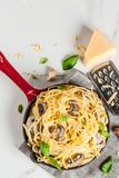 Creamy mushroom pasta. With cheese and basil, in portioned frying pan, on white marble table, copy space top view Royalty Free Stock Photo