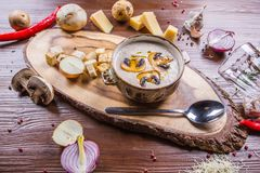 Creamy mushroom soup in a ceramic plate on a wooden stand stock image