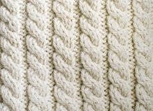 Creamy off-white wool knitwork. Cream white off-white handmade wool knitwork. Creamy off-white wool knitwork full frame for warming artisan backdrop or Stock Images