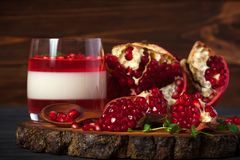 Creamy panna cotta with red jelly in beautiful glasses, fresh ripe pomegranate on wooden background. Delicious Italian dessert. Ho. Creamy panna cotta with red stock image