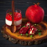Creamy panna cotta with red jelly in beautiful glasses, fresh ripe pomegranate on wooden background. Delicious Italian dessert. Ho. Creamy panna cotta with red Royalty Free Stock Photo