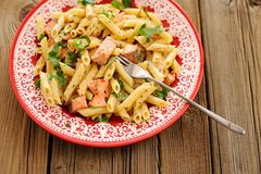 Creamy pasta with salmon and parsley in red plate, copyspace Royalty Free Stock Image