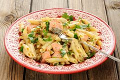 Creamy pasta with salmon and parsley in red plate Stock Photos