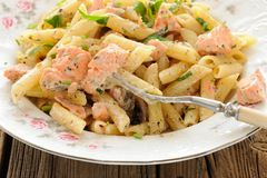 Creamy pasta with salmon and parsley in white plate closeup macr Royalty Free Stock Photos