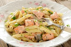 Creamy pasta with salmon and parsley in white plate Stock Image