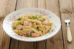 Creamy pasta with salmon and parsley in white plate Stock Photography