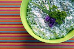 Creamy pea salad with garlic yogurt, decorated with blossoms of chives, parsley and colorful pepper. royalty free stock photography