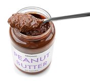 Creamy peanut butter in spoon and jar. On white background Royalty Free Stock Photography