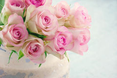 Pink roses in a shabby chic metal bucket. Creamy pink roses in a shabby chic metal bucket on vintage wooden background Royalty Free Stock Photo