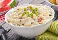 Creamy Potato Salad. A delicious homemade creamy potato salad on a rustic picnic table stock photo