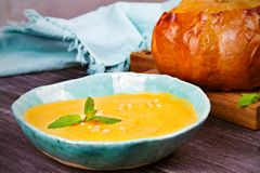 Creamy pumpkin or butternut squash soup in a bowl, whole roasted pumpkin on wooden background. Stock Images