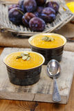 Creamy pumpkin dessert on wooden table. Raw plums in wicker basket in the background Royalty Free Stock Image