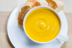 Creamy pumpkin soup with lightly toasted baguette. A cup of creamy pumpkin soup with lightly toasted baguette slices Stock Images