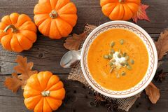 Pumpkin soup, overhead rustic autumn table scene. Creamy pumpkin soup, rustic autumn table scene, overhead view on aged wood stock photography