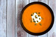 Creamy pumpkin soup on a rustic wood background Royalty Free Stock Photo