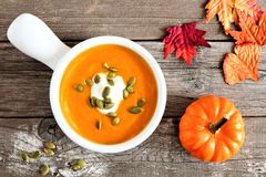 Creamy pumpkin soup on rustic wood background Royalty Free Stock Photos