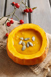 Creamy pumpkin soup on rustic wooden table Royalty Free Stock Photo