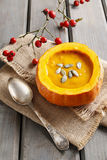 Creamy pumpkin soup on rustic wooden table Royalty Free Stock Images
