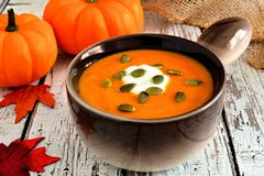 Creamy pumpkin soup topped with pumpkin seeds and cream Royalty Free Stock Image