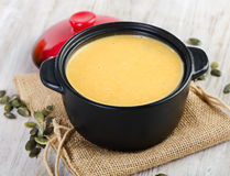 Creamy pumpkin soup on a wooden table Royalty Free Stock Photos
