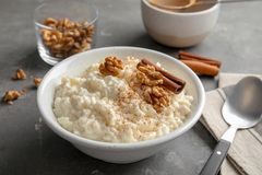 Creamy rice pudding with cinnamon and walnuts in bowl served on table. Creamy rice pudding with cinnamon and walnuts in bowl served on grey table royalty free stock photography