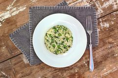 Creamy risotto with peas and spinach on white plate on grey cloth on rustic table Stock Photography