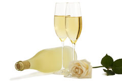 Creamy rose in front of two champagne glasses and Stock Images