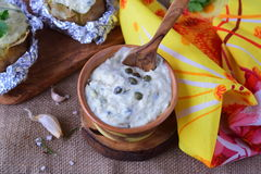 Creamy sause with yogurt capers. garlic nd olive oil in a ceramic pot on a piece of wood. Royalty Free Stock Image
