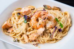 Creamy seafood pasta. With salmon, shrimp, mussels and Grana Padano cheese Stock Images