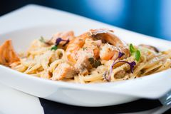 Creamy seafood pasta. With salmon, shrimp, mussels and Grana Padano cheese Stock Photos