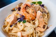 Creamy seafood pasta. With salmon, shrimp, mussels and Grana Padano cheese Stock Photo